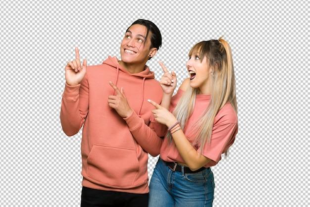 En el día de san valentín pareja joven apuntando con el dedo índice y mirando hacia arriba