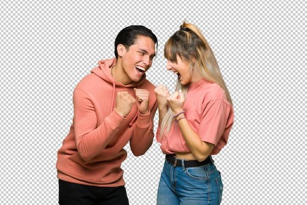 En el día de san valentín pareja joven celebrando una victoria en posición de ganador