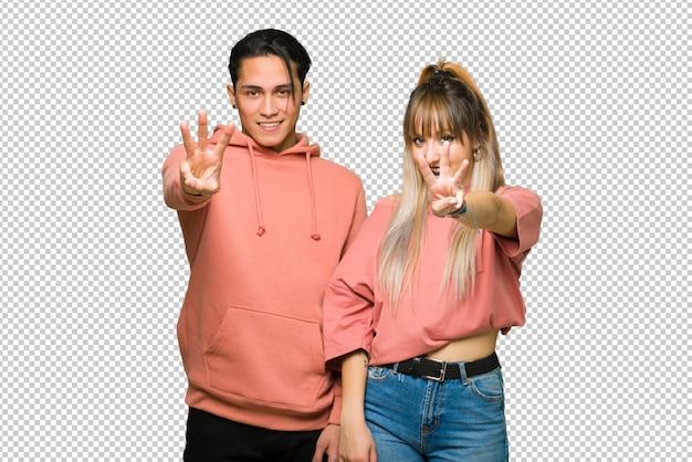 En el día de san valentín pareja joven feliz y contando tres con los dedos.