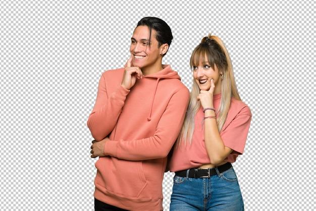 En el día de san valentín pareja joven pensando en una idea mientras mira hacia arriba