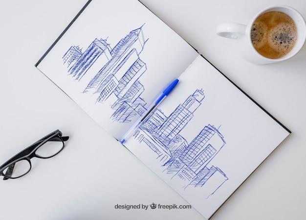 Disegno della penna sul taccuino con gli occhiali e la tazza di caffè