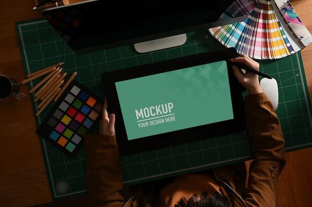 Diseñador gráfico femenino que trabaja con maquetas de tabletas y suministros de diseñador en el escritorio de la computadora