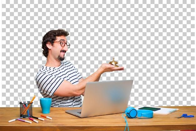 Diseñador gráfico loco joven en un escritorio con una computadora portátil y con una campana del anillo