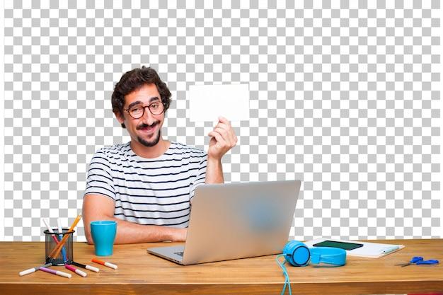 Diseñador gráfico loco joven en un escritorio con una computadora portátil y con un cartel