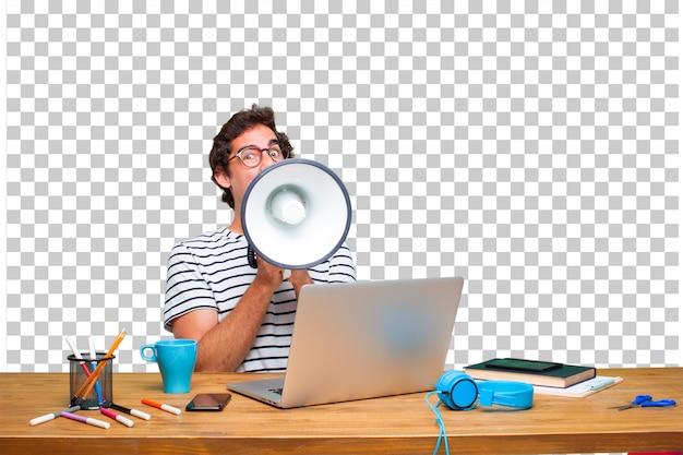 Diseñador gráfico loco joven en un escritorio con una computadora portátil y con un megáfono