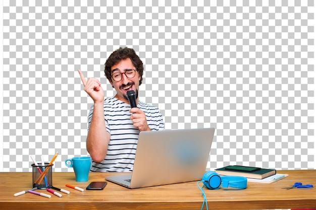 Diseñador gráfico loco joven en un escritorio con una computadora portátil y con un micrófono