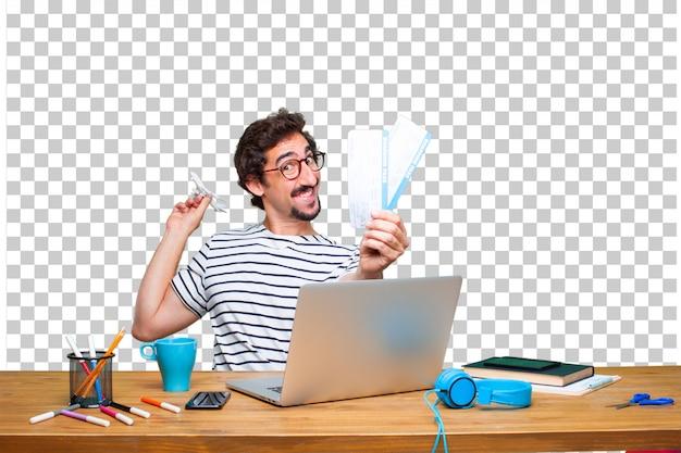 Diseñador gráfico loco joven en un escritorio con una computadora portátil y
