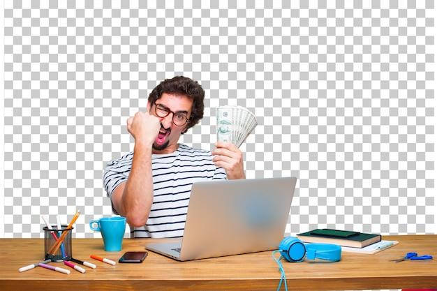 Diseñador gráfico loco joven en un escritorio con un concepto del ordenador portátil y de la paga, de la compra o del dinero