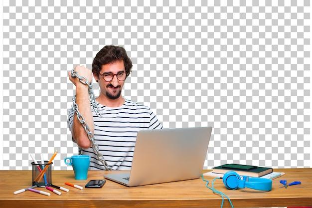 Diseñador gráfico loco joven en un escritorio con un ordenador portátil y con una cadena. concepto de libertad