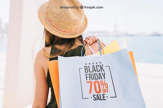 Diseño de mock up con mujer sosteniendo bolsas de compras