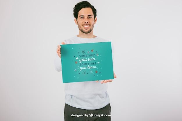 Diseño de mock up con hombre sonriente sujetando un póster