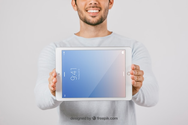 Diseño de mock up con hombre sujetando una tablet en horizontal
