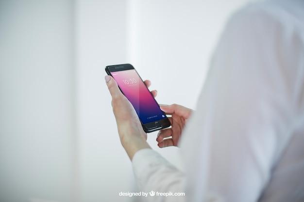 Diseño de mock up de negocios con manos sujetando el móvil