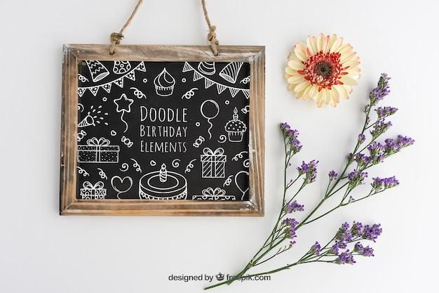 Diseño de mockup con pizarra de cumpleaños y decoración floral