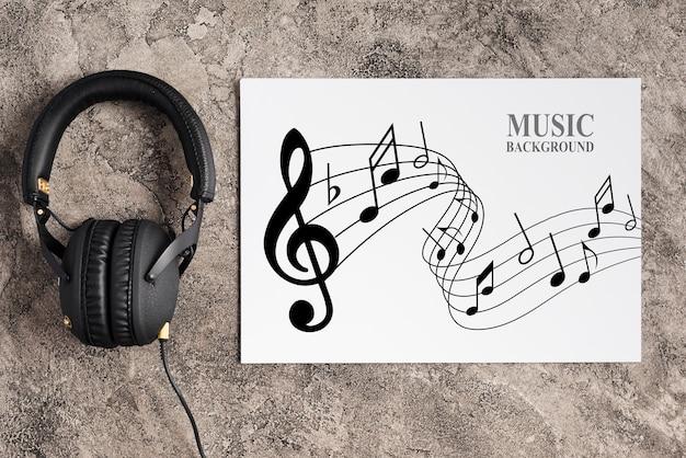 Diseño de música en hoja con auriculares al lado