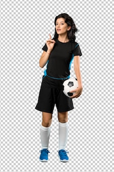Un disparo de cuerpo entero de una joven futbolista con la intención de realizar la solución mientras levanta un dedo.