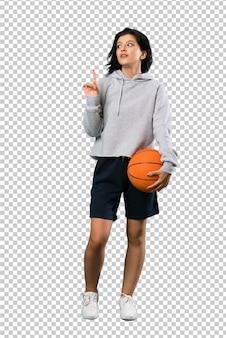 Un disparo de cuerpo entero de una mujer joven que juega al baloncesto con la intención de darse cuenta de la solución mientras levanta un dedo.