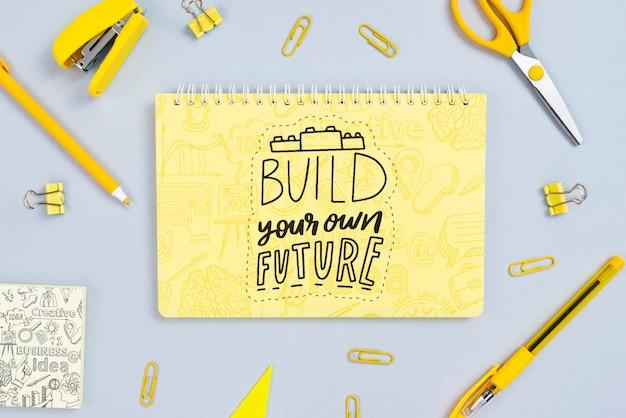 Disposición plana con cuaderno y cita motivacional
