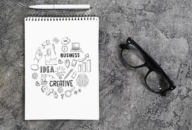 Disposición plana con cuaderno, gafas y bolígrafo.