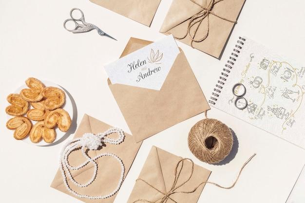 Disposición plana de sobres de papel marrón y anillos de boda