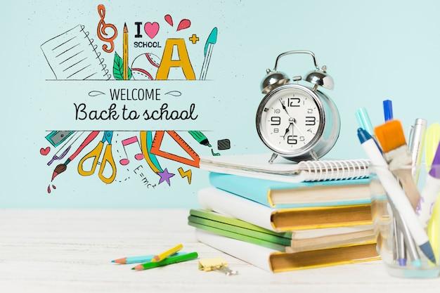 Disposizione con libri scolastici e orologio
