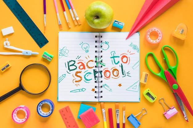 Disposizione con materiale scolastico e taccuino aperto