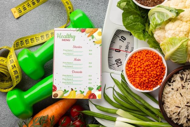 Disposizione di cibi sani su scala e menu dietetico