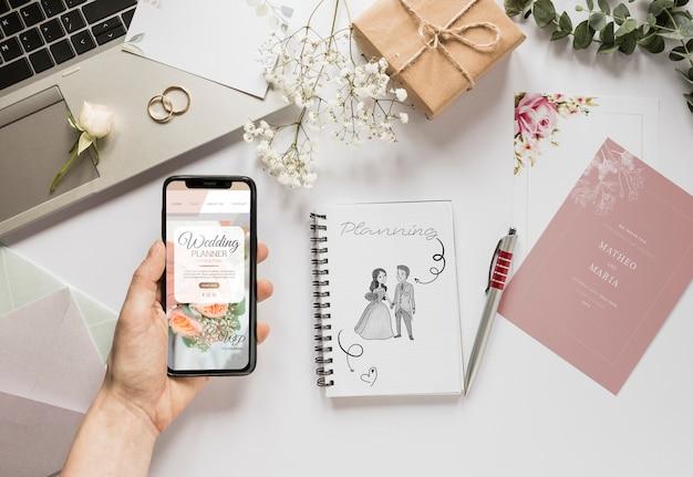 Disposizione grassa della mano che tiene smartphone ed elementi essenziali di nozze