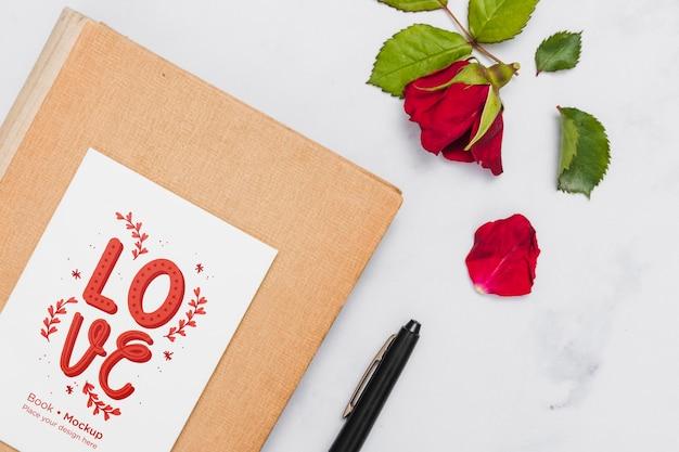 Disposizione piana del libro con rosa e penna