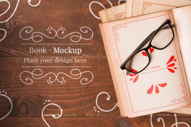 Disposizione piana del libro mock-up con gli occhiali