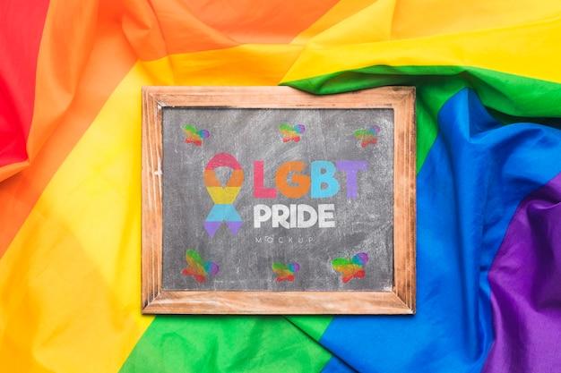 Disposizione piana del tessuto colorato arcobaleno con la lavagna sulla cima