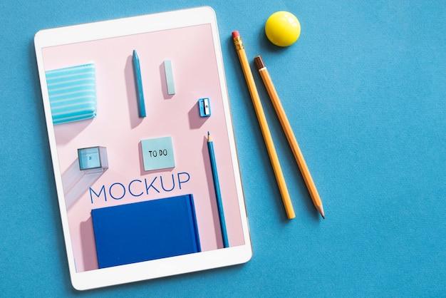 Disposizione vista dall'alto con tablet e matite mock-up