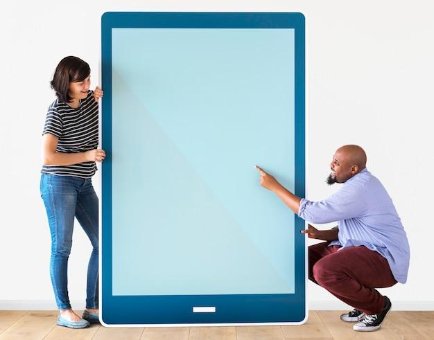 Divers paar dat een tablet met grafiek houdt Premium Psd