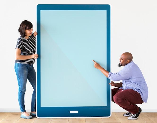 Diversa pareja sosteniendo una tableta con gráficos