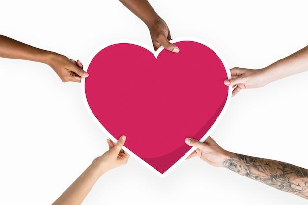 Diversas manos sosteniendo un corazón rojo