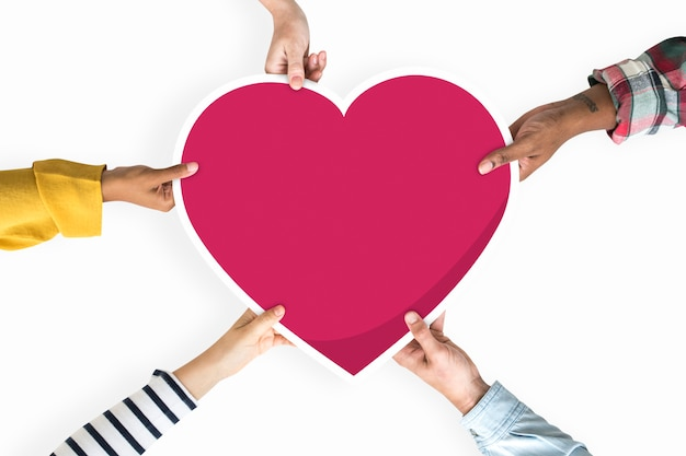 Diverse mani in possesso di un cuore rosso