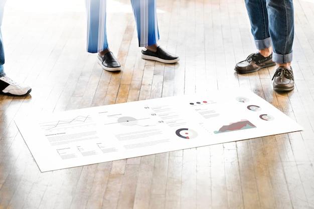 Diverse mensen brainstormen in een workshop over een papieren mockup