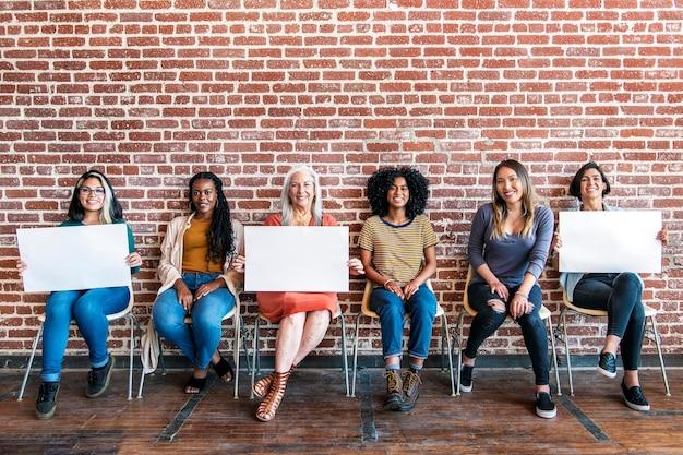 Diverse vrouwen die een leeg affichesjabloon tonen