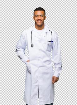 Doctor afroamericano joven del hombre que presenta con los brazos en la cadera y la sonrisa