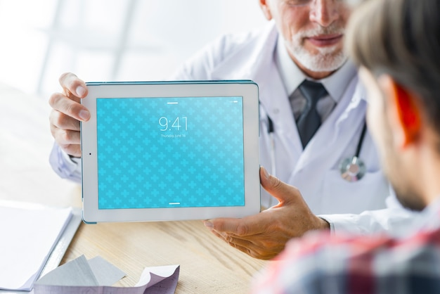 Doctor enseñando tablet al paciente
