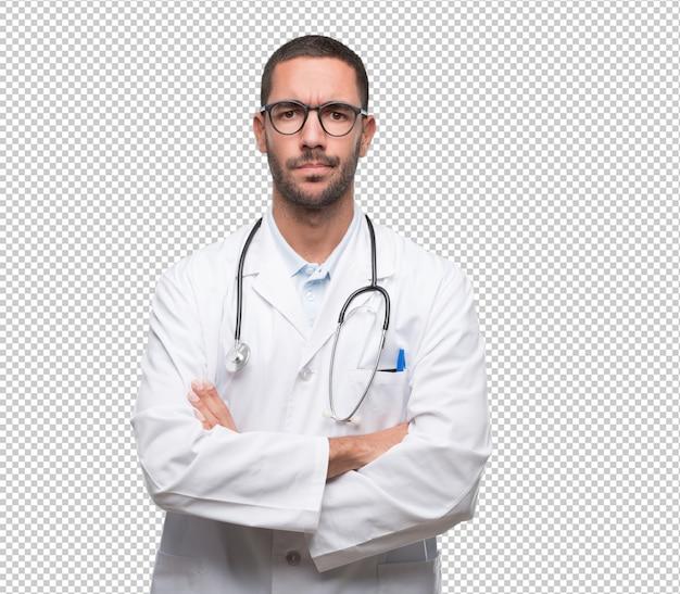 Doctor joven serio con gesto de brazos cruzados