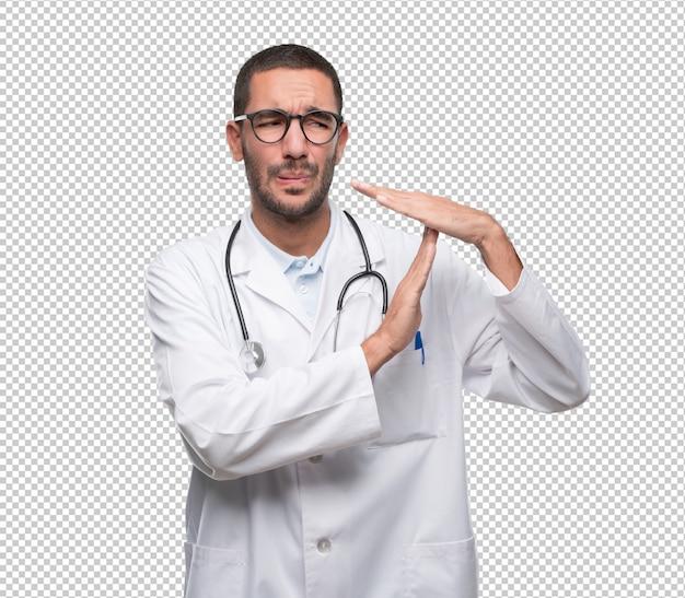 Doctor joven serio haciendo un gesto de descanso