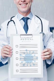 Doctor sonriente sosteniendo una maqueta de papel médico