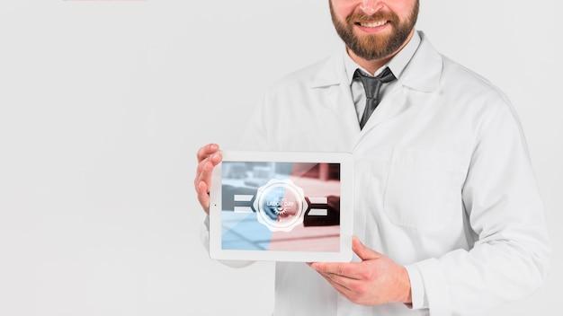 Doctor sujetando maqueta de tableta para el día de trabajo