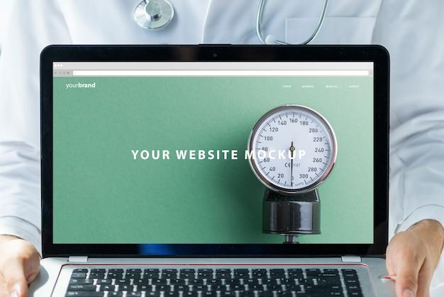 Doctor sujetando mockup de portátil para página web