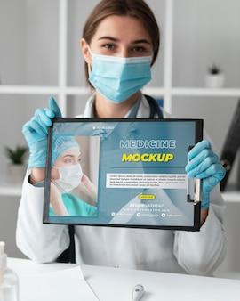 Doctora sosteniendo un portapapeles de maqueta