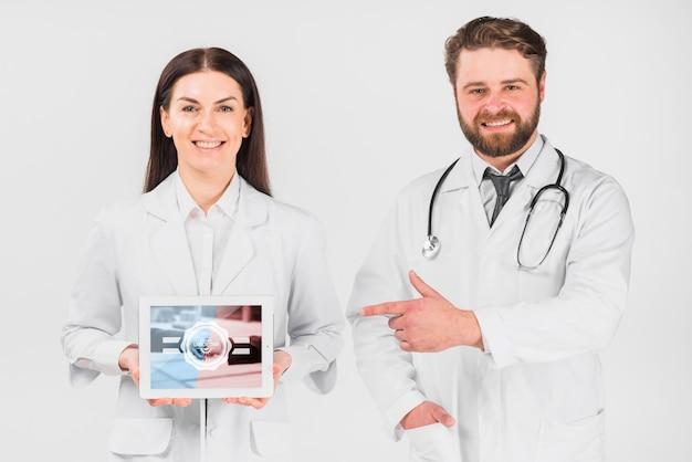 Doctores sujetando maqueta de tableta para el día de trabajo