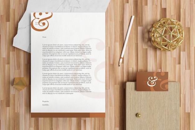 Documento di carta intestata a4 con biglietto da visita e modello di cancelleria nel pavimento di legno