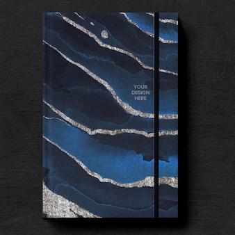 Donkerblauw boekomslagmodel op een zwarte tafel