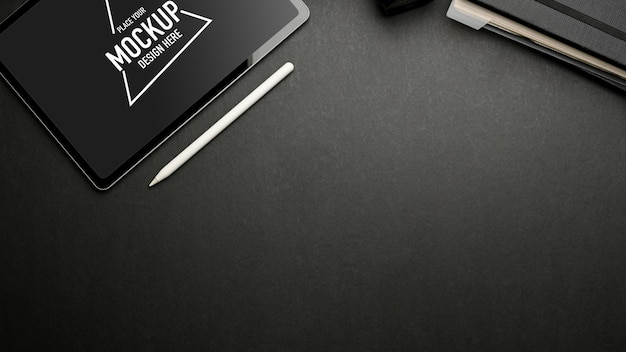 Donkere creatieve plat leggen werkruimte met digitale tablet mockup op donkere tafel